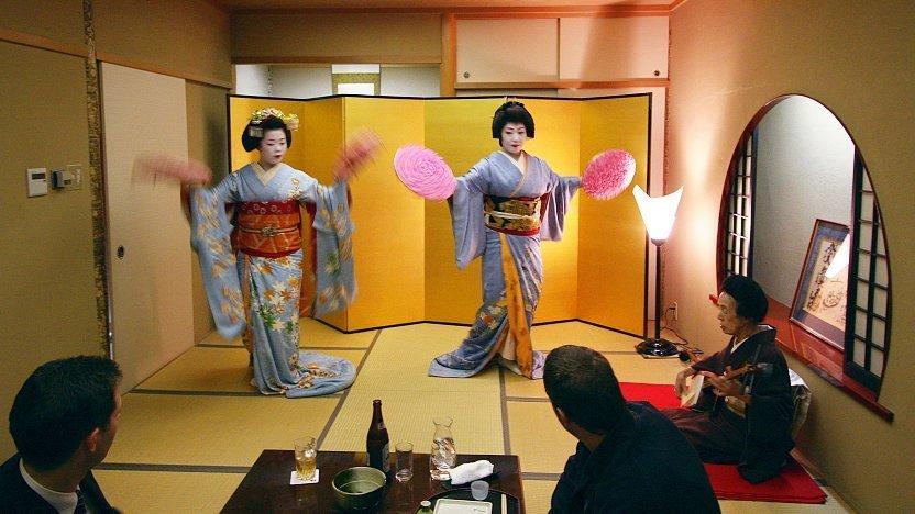 Geishas avec du mascara et en Kimonos, en train de danser devant leurs clients