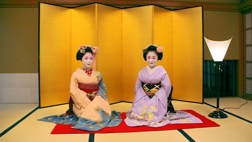 Deux maiko en kimono, avec les sourcils bien travaillés, du rouge à lèvres, du maquillage blanc sur les paupières et le visage